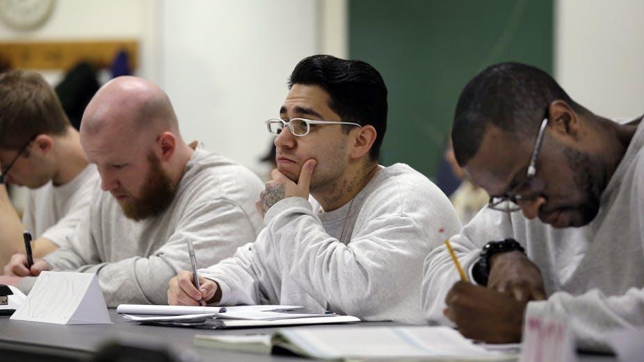 prison education: Men in white sweatshirts sitting at table take notes.